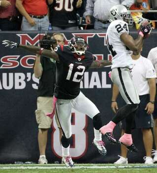 Houston Texans wide receiver Jacoby Jones (12) is surprised to see Oakland Raiders free safety Michael Huff (24) make a game saving interception during the fourth quarter of an NFL football game at Reliant Stadium on Sunday, Oct. 9, 2011, in Houston. The Oakland Raiders won 25-20. Photo: Nick De La Torre, Houston Chronicle / © 2011  Houston Chronicle