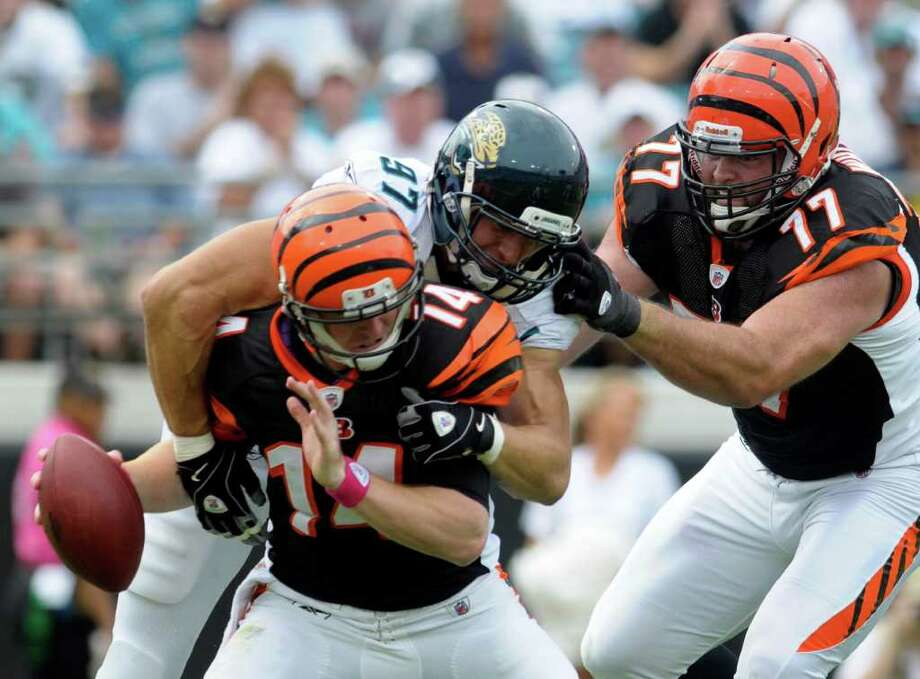Cincinnati Bengals quarterback Andy Dalton (14) is sacked by Jacksonville Jaguars defensive end John Chick (97) after beating Cincinnati Bengals tackle Andrew Whitworth (77) during the first half of an NFL football game in Jacksonville, Fla., Sunday, Oct. 9, 2011. (AP Photo/Phelan M. Ebenhack) Photo: Phelan M. Ebenhack / FR121174 AP