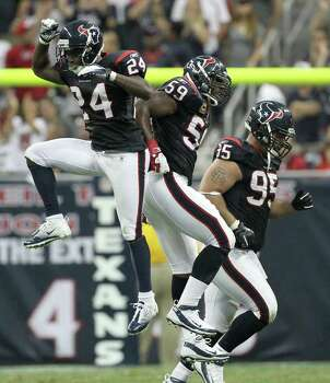 Houston Texans cornerback Johnathan Joseph (24) and Houston Texans inside linebacker DeMeco Ryans (59) engage in a glorified high five as they force the Oakland Raiders to punt in the fourth quarter of an NFL football game at Reliant Stadium on Sunday, Oct. 9, 2011, in Houston. The Oakland Raiders won 25-20. Photo: Nick De La Torre, Houston Chronicle / © 2011  Houston Chronicle