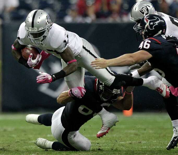 Oakland Raiders wide receiver Denarius Moore (17) is tripped up by Houston Texans tight end James Ca