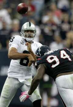 Oakland Raiders quarterback Jason Campbell (8) throws a pass over Houston Texans defensive end Antonio Smith (94) during the third quarter of an NFL football game at Reliant Stadium on Sunday, Oct. 9, 2011, in Houston. The Raiders beat the Texans 25-20. Photo: Brett Coomer, Houston Chronicle / © 2011  Houston Chronicle