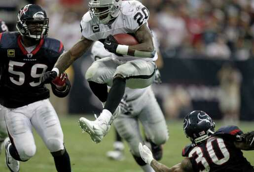 Oakland Raiders running back Darren McFadden (20) leaps between Houston Texans inside linebacker DeMeco Ryans (59) and Texans cornerback Jason Allen (30) during the third quarter of an NFL football game at Reliant Stadium on Sunday, Oct. 9, 2011, in Houston. The Raiders beat the Texans 25-20. Photo: Brett Coomer, Houston Chronicle / © 2011  Houston Chronicle