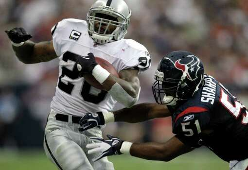 Oakland Raiders running back Darren McFadden (20) is knocked out of bounds by Houston Texans linebacker Darryl Sharpton (51) second quarter of an NFL football game at Reliant Stadium on Sunday, Oct. 9, 2011, in Houston. Photo: Brett Coomer, Houston Chronicle / © 2011  Houston Chronicle