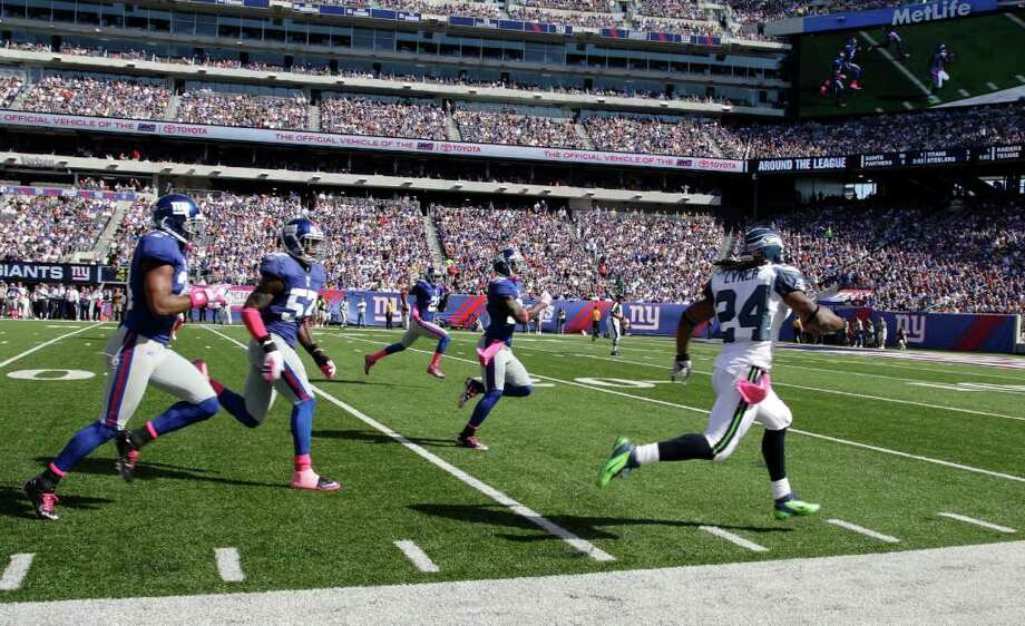 Seattle Seahawks running back Marshawn Lynch (24) runs away from New York Giants defenders Terrell Thomas, left, Jacquian Williams (57) and others for a touchdown during the first quarter of an NFL football game Sunday, Oct. 9, 2011, in East Rutherford, N.J. (AP Photo/Julio Cortez) Photo: Julio Cortez / AP