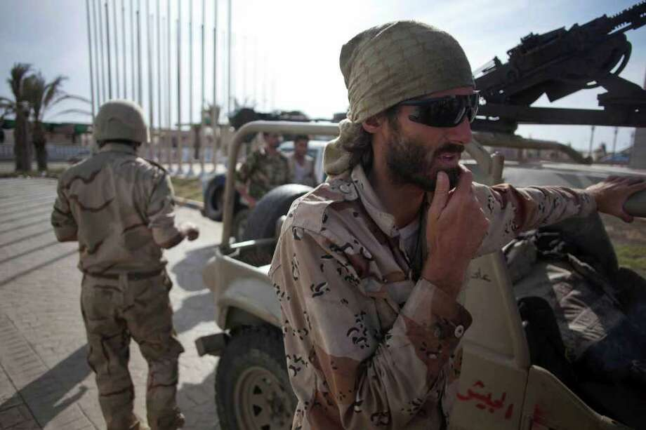 Matthew VanDyke, a writer and filmmaker from Baltimore, Md. who has joined with revolutionary fighters, is seen on the front line in Sirte, Libya, Thursday, Oct. 6, 2011. VanDyke was freed from Libya's most notorious prison in August during the turmoil of the uprising against Moammar Gadhafi after his capture in March by government soldiers.(AP Photo/Manu Brabo) Photo: Manu Brabo / AP