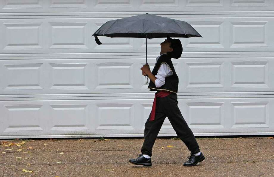 Yianna Garcia, 9, basks in the rain as he steps out ahead of his family on their way to the Greek Festival. Photo: James Nielsen / © 2011 Houston Chronicle