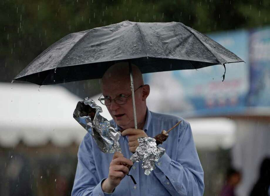 Price Lewis eats Souvlaki under his umbrella as he enjoys the Original Greek Festival, which waived its entry fee Sunday to bring people out in the rain. Photo: James Nielsen / © 2011 Houston Chronicle