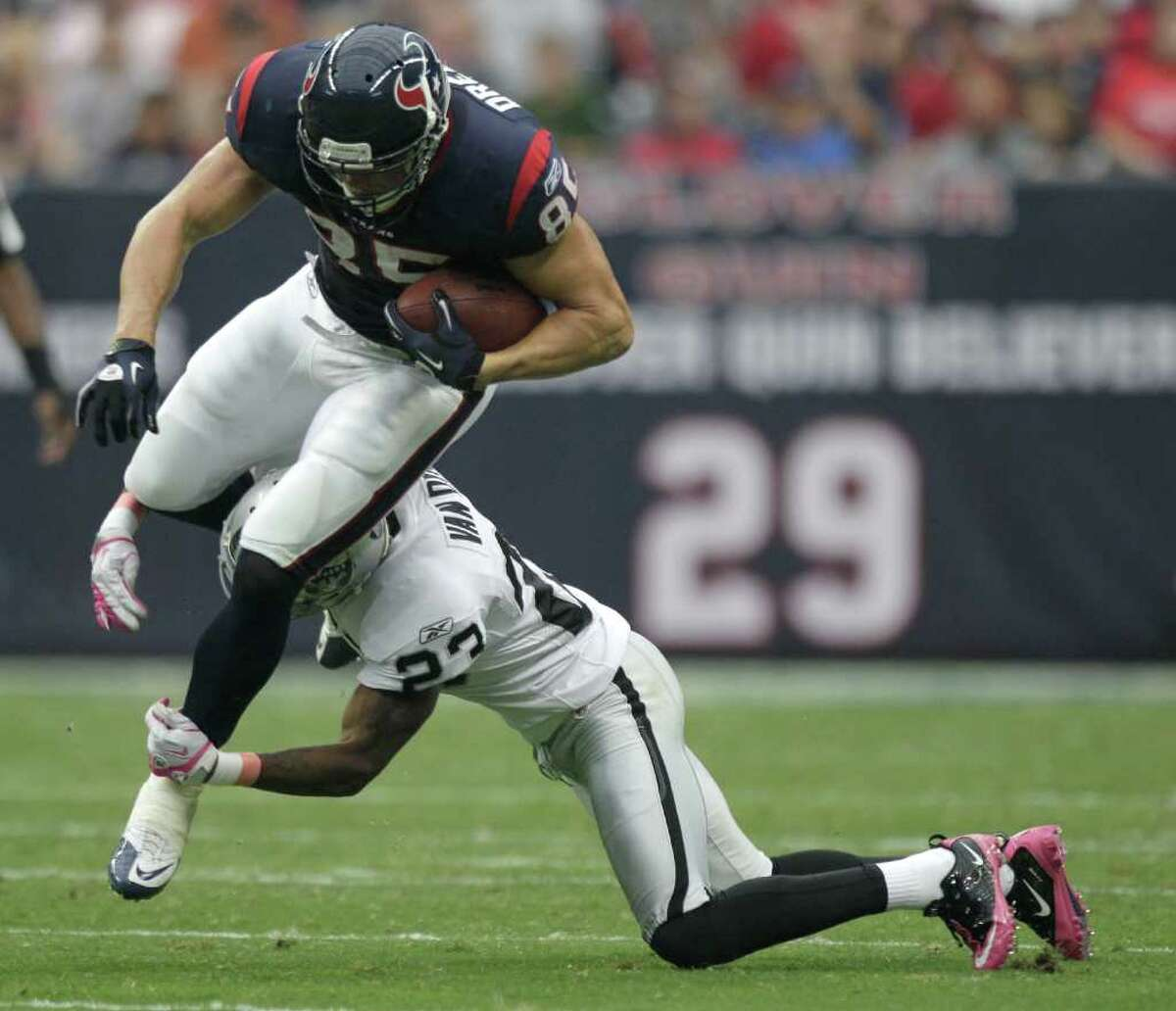 Houston Texans tight end Joel Dreessen (85) is tripped up by Oakland Raiders defensive back DeMarcus Van Dyke (23) after a catch during the first quarter of an NFL football game at Reliant Stadium on Sunday, Oct. 9, 2011, in Houston. ( Brett Coomer / Houston Chronicle )