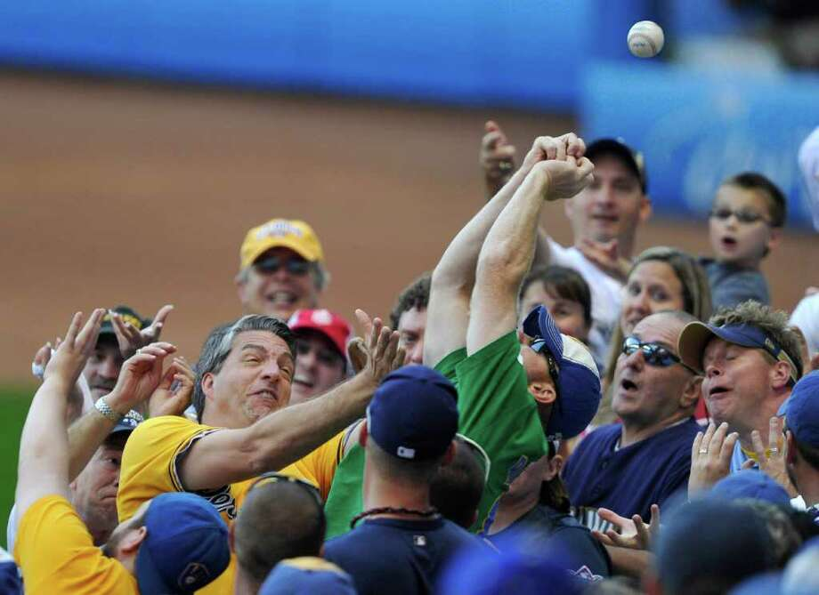 Fans go after a foul ball hit by Milwaukee Brewers' Rickie Weeks during the sixth inning of Game 1 of baseball's National League championship series against the St. Louis Cardinals Sunday, Oct. 9, 2011, in Milwaukee. (AP Photo/Jim Prisching) Photo: Jim Prisching, Associated Press / FR59933 AP