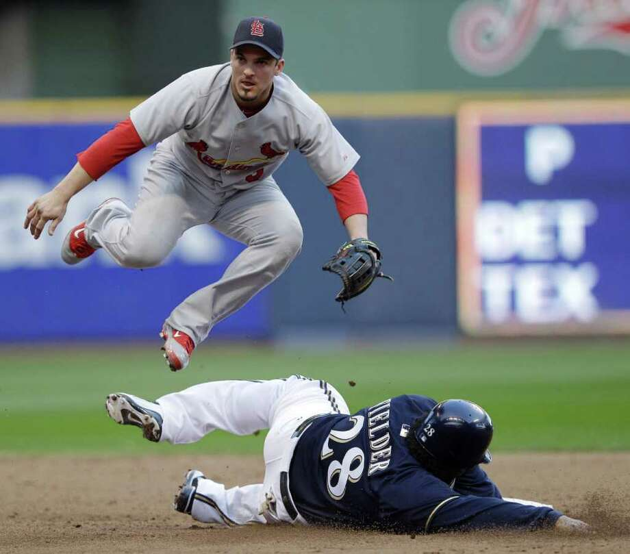 St. Louis Cardinals second baseman Ryan Theriot leaps over Milwaukee Brewers' Prince Fielder (28) to turn a double play on a ball hit by Rickie Weeks during the sixth inning of Game 1 of baseball's National League championship series Sunday, Oct. 9, 2011, in Milwaukee. (AP Photo/David J. Phillip) Photo: David J. Phillip, Associated Press / AP