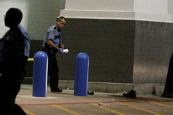 Houston Police officer investigate a shooting in front of the Academy Sports and Outdoors store in the 7600 block of Westheimer Sunday, Oct. 9, 2011, in Houston. ( James Nielsen / Chronicle )