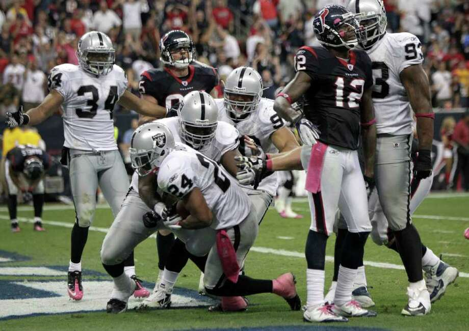 Brett coomer: Chronicle MAN OF THE HOUR: Raiders players mob free safety Michael Huff (24) after the former Texas Longhorns star intercepted a Matt Schaub pass to seal Oakland's win Sunday at Reliant Stadium. Photo: Brett Coomer / © 2011  Houston Chronicle