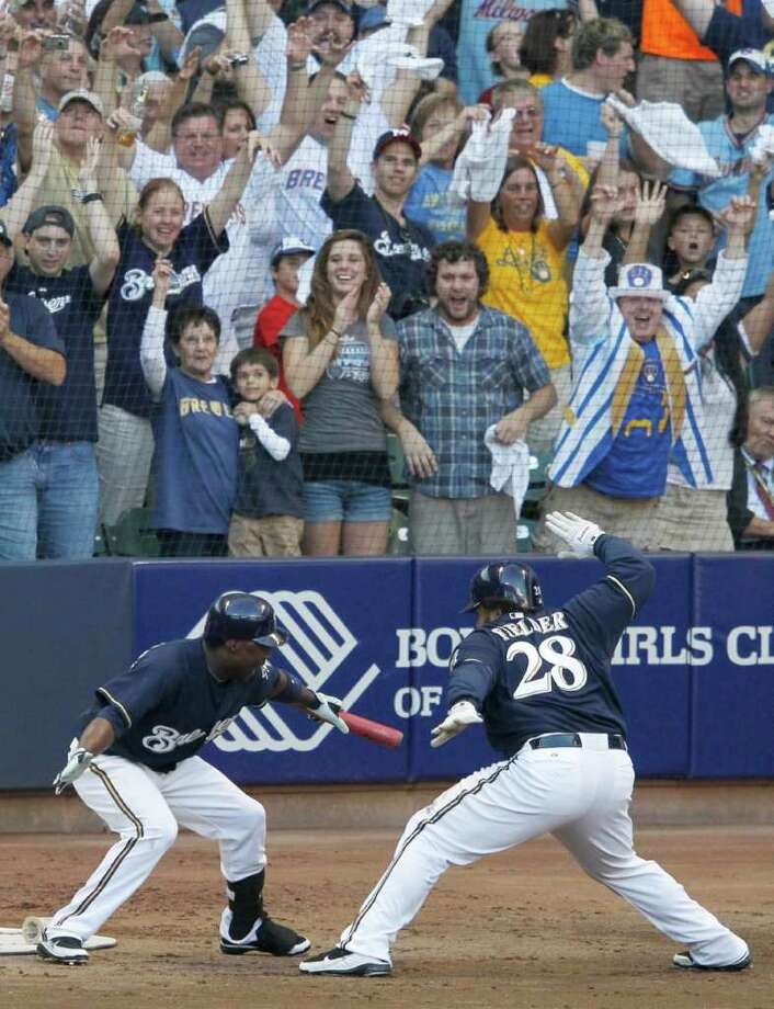 JEFF ROBERSON: ASSOCIATED PRESS BANG, BANG: Milwaukee fans enjoy the antics of Yuniesky Betancourt, left, and Prince Fielder during a six-run fifth inning in which both players homered. Photo: Jeff Roberson / AP