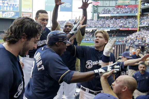 Milwaukee Brewers' Yuniesky Betancourt is congratulated in the dugout after hitting a two-run home run during the fifth inning of Game 1 of baseball's National League championship series against the St. Louis Cardinals Sunday, Oct. 9, 2011, in Milwaukee. (AP Photo/David J. Phillip)