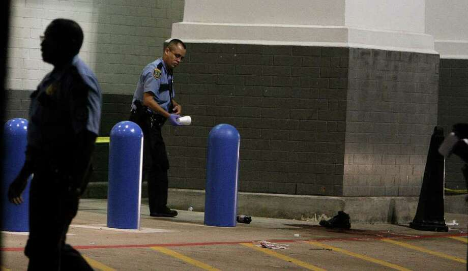 Houston Police officer investigate a shooting in front of the Academy Sports and Outdoors store in the 7600 block of Westheimer Sunday, Oct. 9, 2011, in Houston. ( James Nielsen / Chronicle ) Photo: James Nielsen / © 2011 Houston Chronicle