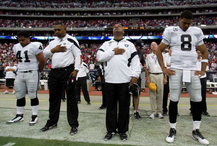 Brett Coomer: Chronicle XXXXXXXXXXX: Oakland Raiders head coach Hue Jackson, right center, and his players pause for a moment of silence for Oakland Raiders owner Al Davis, who died Saturday morning, at the start of an NFL football game at Reliant Stadium on Sunday, Oct. 9, 2011, in Houston. ( Photo: Brett Coomer / © 2011  Houston Chronicle
