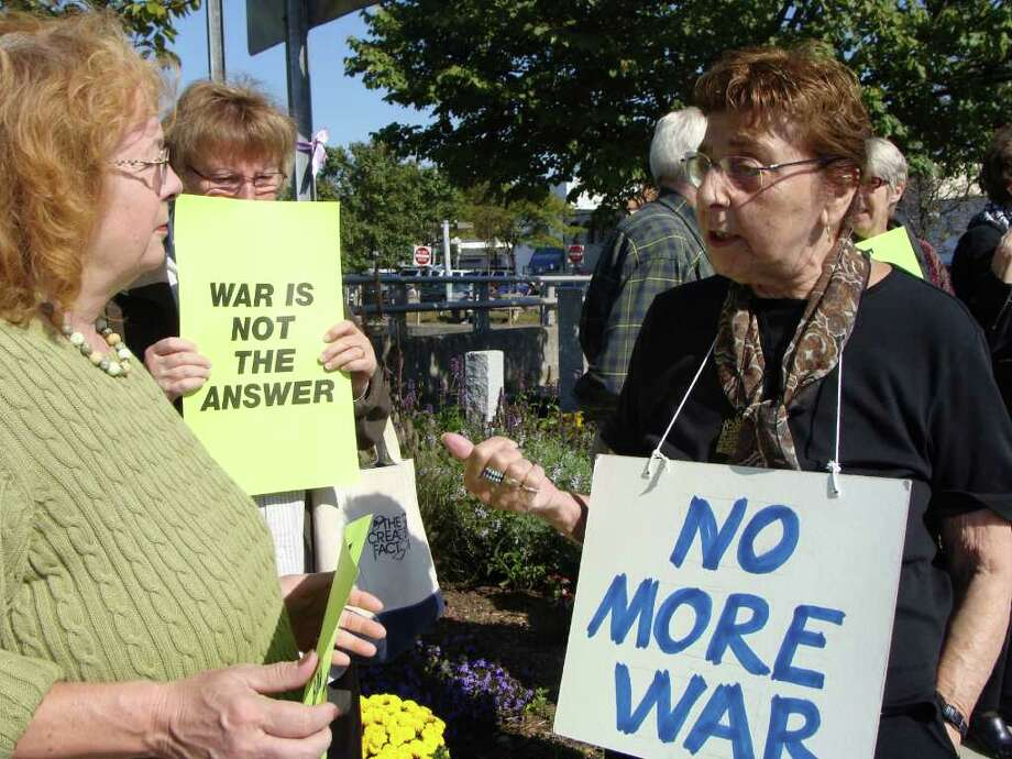 """Estelle Margolis, the widow of Emanuel """"Manny"""" Margolis, a civil-rights lawyer and first amendment advocate who died in August, wears a sign, ìNo more wa,rî during a peace vigil on the Route 1 bridge over the Saugatuck River in downtown Westport Saturday as she talks with Suzanne Sheridan of Westport. The vigil preceded a memorial service for Manny Margolis at the Westport Public Library. Photo: Meg Barone"""