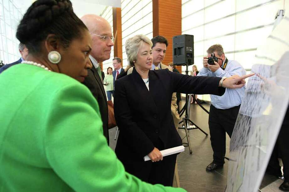 Mayor Annise Parker points out a location on a map detailing the GREENLINK bus route with Bob Eury, Executive Director of Houston Downtown Management District, center, and Congresswoman Sheila Jackson Lee after a press conference in the lobby of BG Group Place. The Houston Downtown Management District (Downtown District), together with BG Group and Houston First Corporation, announced the details of the new GREENLINK bus service.  The new environmentally friendly buses will hit the streets in May 2012 with a 2.5 mile route that will connect major office buildings along Smith and Louisiana streets to METRO transit, the convention corridor, hotels, shopping, restaurants and our civic center. Photo: Karen Warren, Houston Chronicle / © 2011 Houston Chronicle