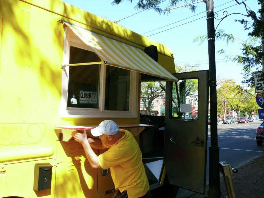 Christophe Ensenat sets up his mobile crepe truck outside the Fairfield Public Library on the Post Road. Photo: Genevieve Reilly / Fairfield Citizen