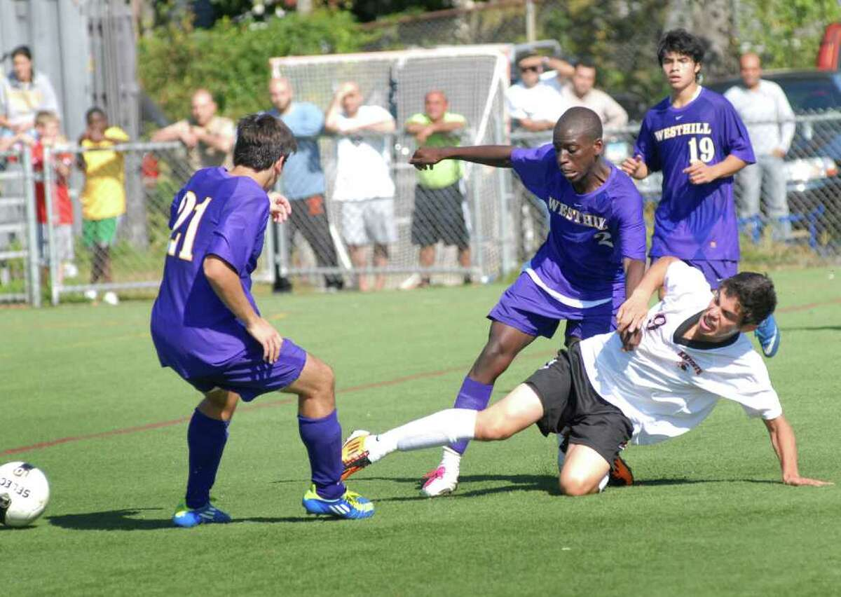 Westhill's Nicholas Mallozzi (21), Brandon Carter (2) and Diego Calderon (19) and Stamford' Vlad Zdyr (9) at boys soccer game, Westhill High School @ Stamford High School in Stamford, Conn. on Monday October 10, 2011.
