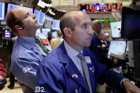 Specialist James Denaro, right, works on the floor of the New York Stock Exchange Monday, Oct. 10, 2011. (AP Photo/Richard Drew)