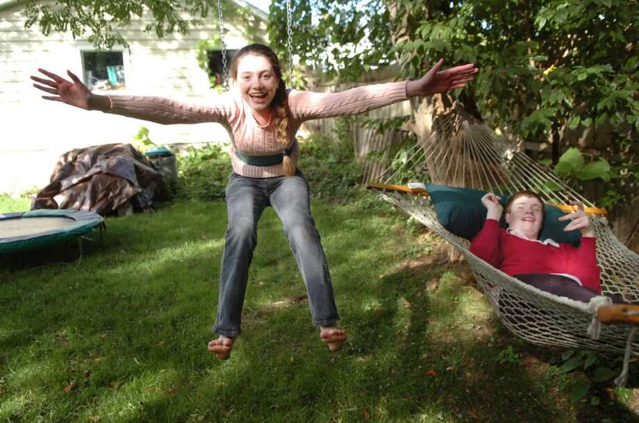 Cos Cob, Oct.6, 2009. Rose Arezinis, 14 and her autistic brother Karl play outside on the hammock and swing. Photo: Helen Neafsey / Greenwich Time