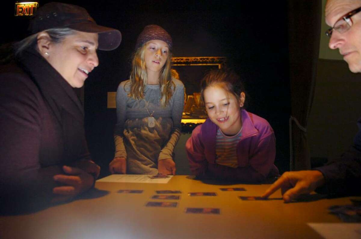 Greenwich, Oct. 18, 2009. Amy Rabenhorst, daughter Anika, 9, friend Isabella Danino and husband Randy Rabenhorst playing a game of alchemy concentration at the Bruce Museum in conjunction with the new exhibition