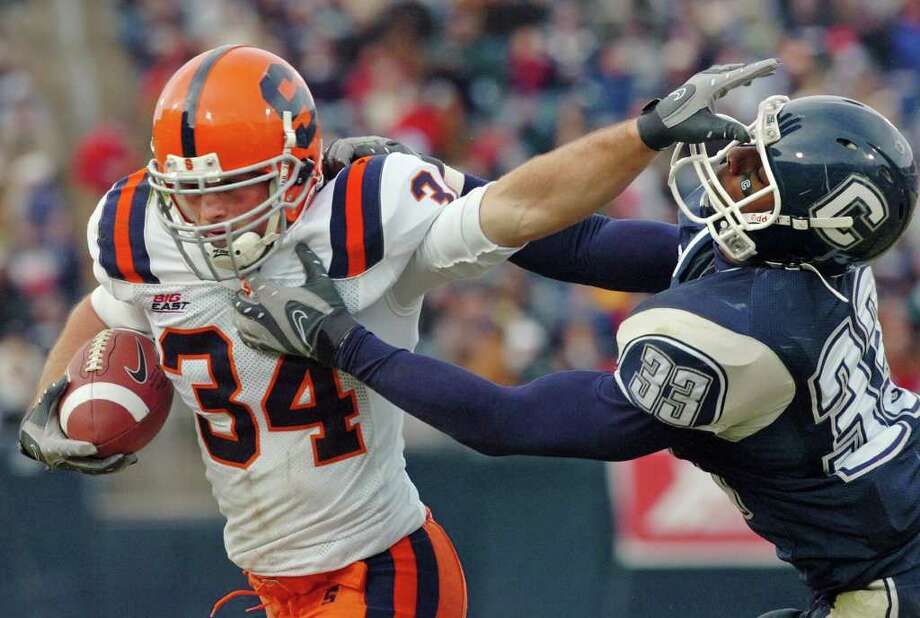 "In this Nov. 17, 2007, file photo, Syracuse's Paul Chiara eludes a tackle attempt by Connecticut's Robert Vaughn during an NCAA college football game in East Hartford, Conn., on Saturday, Nov. 17, 2007. Connecticut coach Pasqualoni says maintaining the school's rivalry with Syracuse should be a ""big factor"" in UConn's decision on whether to try and join the Orange in leaving the Big East for the Atlantic Coast Conference. Pasqualoni says he has not talked to UConn president Susan Herbst or other administration officials about the conference shakeup since Syracuse and Pittsburgh announced they are leaving. (AP Photo/Fred Beckham, File) Photo: Fred Beckham, Associated Press / AP2007"