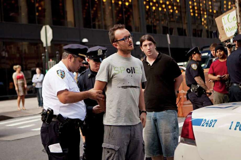 Laurentiu Garofeanu, right, is arrested by  New York City police officers outside Zuccotti Park, Monday, Oct. 10, 2011, in New York. Garofeanu, who returned to the park after his arrest, said he and a second man were charged with disorderly conduct and released after approximately two hours. Garofeanu says he was taking photos of police officers when he was apprehended.  (AP Photo/Andrew Burton) Photo: Andrew Burton / FRE170478 AP