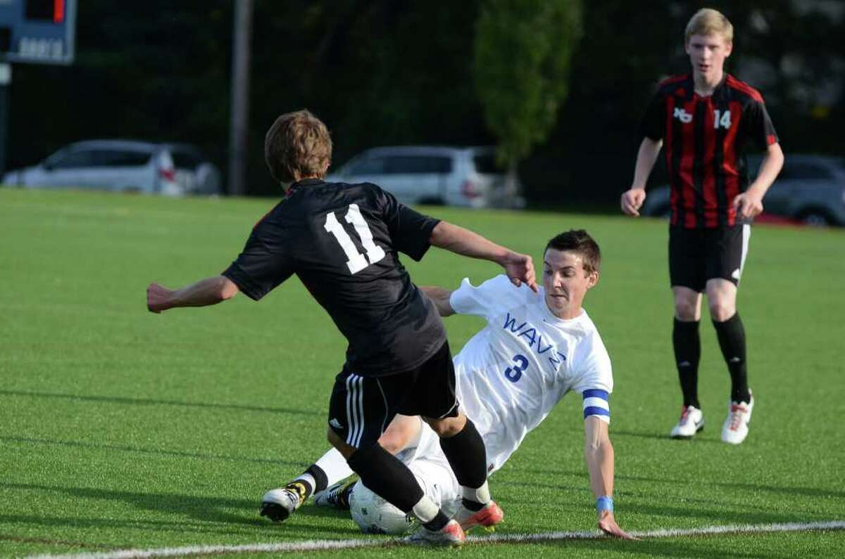 Darien's Eric Kanigan (3) tackles the ball from New Canaan's Steven Valente (11) during the boys soccer game at Darien High School on Monday, Oct. 10, 2011.