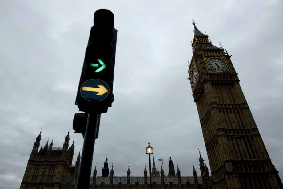 A traffic light illuminates next to the Big Ben clock tower in London, Monday, Oct. 10, 2011.  Big Ben has a little bend.  Experts say the world-famous neogothic clock tower is listing gently, and documents recently published by Britain's Parliament show that the top of its gilded spire is about one-and-a-half feet (nearly half a meter) out of line.  The tower, colloquially known as Big Ben after its massive bell - has been slightly off center since it was erected in the 19th century. Like many old buildings its position has been shifting imperceptibly for years as the ground beneath it subsides.  (AP Photo/Matt Dunham) Photo: Matt Dunham / AP