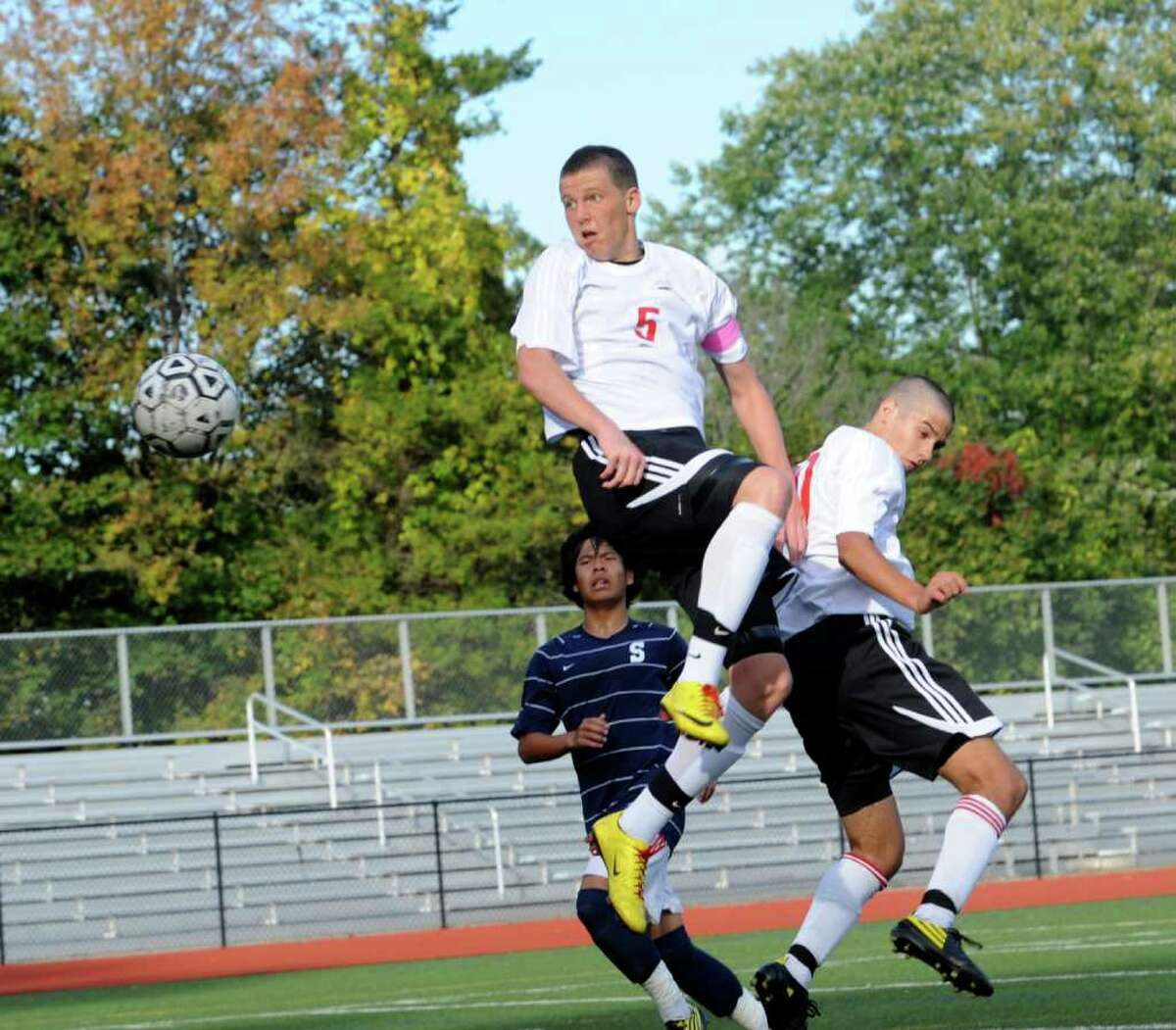 Will Gittings #5 and Ryan Flippin #21 of Greenwich High School battle Staples' Alex Tonsberg #16 for the ball during Monday's game at Cardinal Stadium. Staples rallied from a 2-0 deficit to beat Greenwich 3-2.
