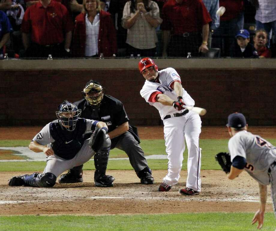 Texas Rangers' Nelson Cruz hits a grand slam home run off of the Detroit Tigers' Ryan Perry, right, to win Game 2 of baseball's American League championship series 7-3,  Monday, Oct. 10, 2011, in Arlington, Texas. The Tigers' Alex Avila catches and home plate umpire Larry Vanover look on. (AP Photo/Eric Gay) Photo: Eric Gay, Associated Press / AP