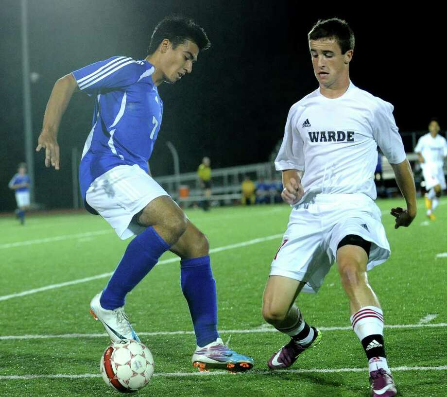 Ludlowe's Christian Barral, left, handles the ball against Warde's Kevin Ross during their matchup at Warde on Monday, October 10, 2011. Photo: Brian A. Pounds / Connecticut Post