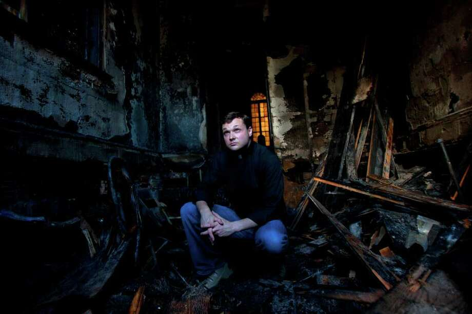 "The Rev. Evan McClanahan inspects the burned church in 2011. ""If I have any advice for pastors,"" says McClanahan, ""it's to make sure you have good fire insurance. And I'm not just talking about Hell."" • More: Church has much to celebrate Photo: Cody Duty / © 2011 Houston Chronicle"
