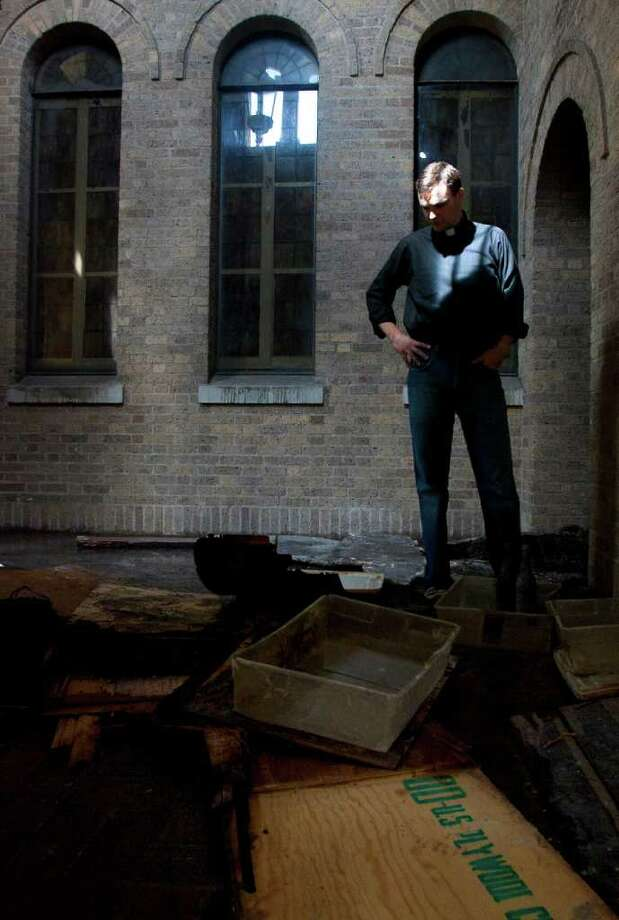 "The Rev. Evan McClanahan looks at the charred remains of the church on Oct. 10, 2011. ""I'm thankful that firefighters got here as quick as they did,"" McClanahan said then. Photo: Cody Duty / © 2011 Houston Chronicle"
