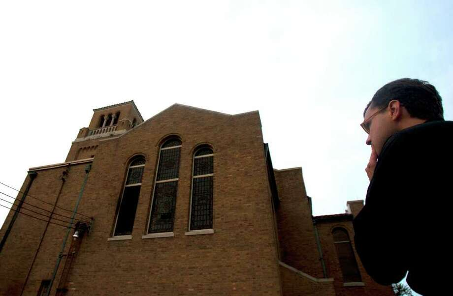 The Rev. Evan McClanahan looks at the First Evangelical Lutheran Church after firefighters extinguished the blaze. Photo: Cody Duty / © 2011 Houston Chronicle