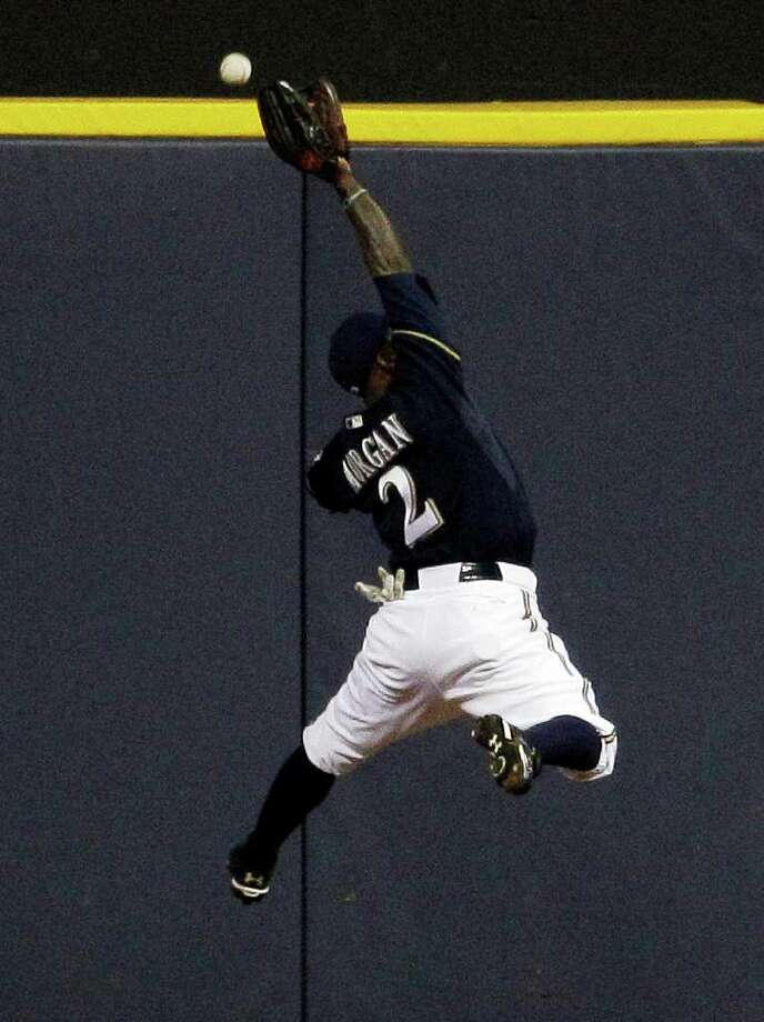 MATT SLOCUM: AP EXTRA, EXTRA: The Brewers' Nyjer Morgan fails to come up with a double by Albert Pujols in the third inning, one of Pujols' three doubles in five at-bats. Photo: Matt Slocum / AP