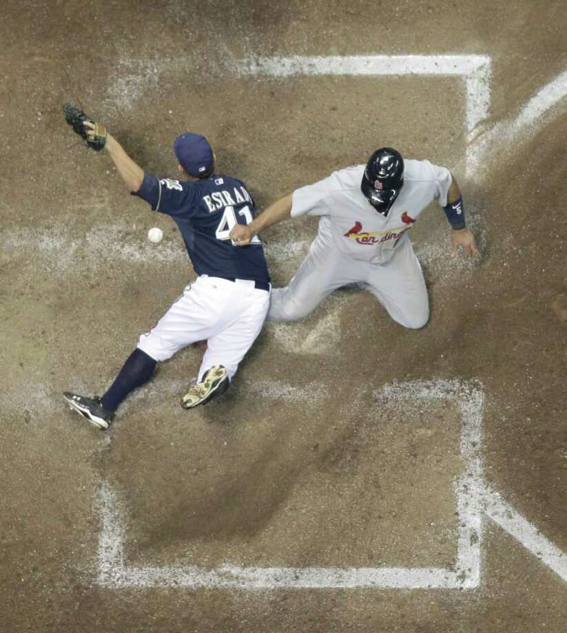 St. Louis Cardinals' Albert Pujols (5) slides safely past Milwaukee Brewers' Marco Estrada (41) to score during the fifth inning of Game 2 of baseball's National League championship series Monday, Oct. 10, 2011, in Milwaukee. (AP Photo/Matt Slocum) Photo: Matt Slocum, Associated Press / AP
