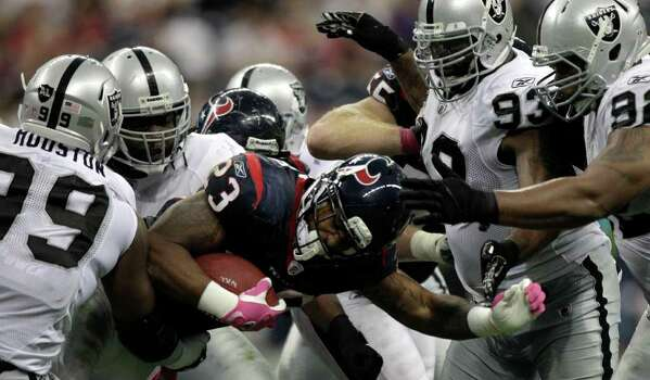 Houston Texans running back Arian Foster (23) is swarmed by Oakland Raiders defender during the third quarter of an NFL football game at Reliant Stadium on Sunday, Oct. 9, 2011, in Houston. The Raiders beat the Texans 25-20. Photo: Brett Coomer, Houston Chronicle / © 2011  Houston Chronicle
