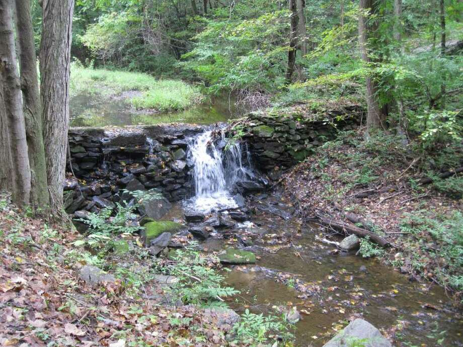 Water spills over a small dam at North Pond in the Grace Richardson Conservation Area. The 87-acre open space both looks and feels different in autumn than it does under a canopy of green in summer, Photo: Contributed Photo / Fairfield Citizen contributed