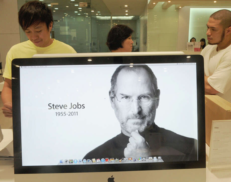Sales clerks work at an Apple store in Manila as a placard  mourns the death of Apple co-founder and chairman Steve Jobs on Oct. 7, 2011. (Jay Directo / AFP / Getty Images)