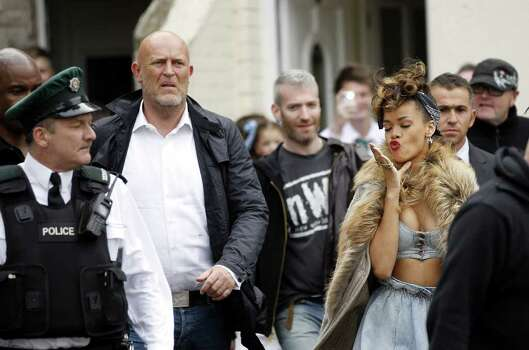 "Pop star Rihanna, right, arrives for filming in the New Lodge area of North Belfast, Northern Ireland, Tuesday, Sept. 27, 2011. Northern Ireland farmer Alan Graham says he doesn't know who Rihanna is but she must keep her top on while performing on his land. Graham says he enforced a dress code as he watched Rihanna shoot a video Monday in his wheat field in Bangor, east of Belfast, for her new single, ""We Found Love."" She's in Northern Ireland this week to perform three concerts. Photo: Peter Morrison, AP / AP"