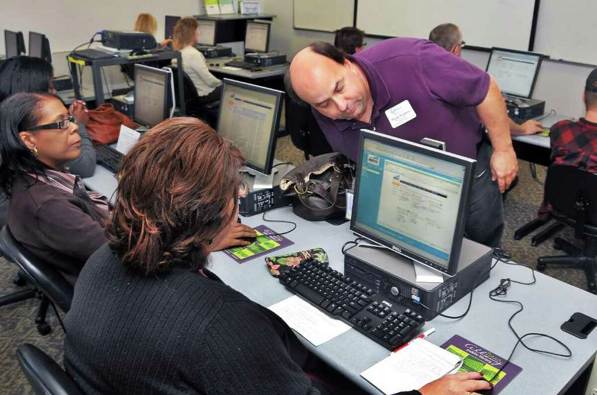 Metrix class instructor Wayne Pombrio (standing) of Albany City youth and workforce services conducts computer training in the Albany Public Library's computer lab in September 2010. (John Carl D'Annibale / Times Union)