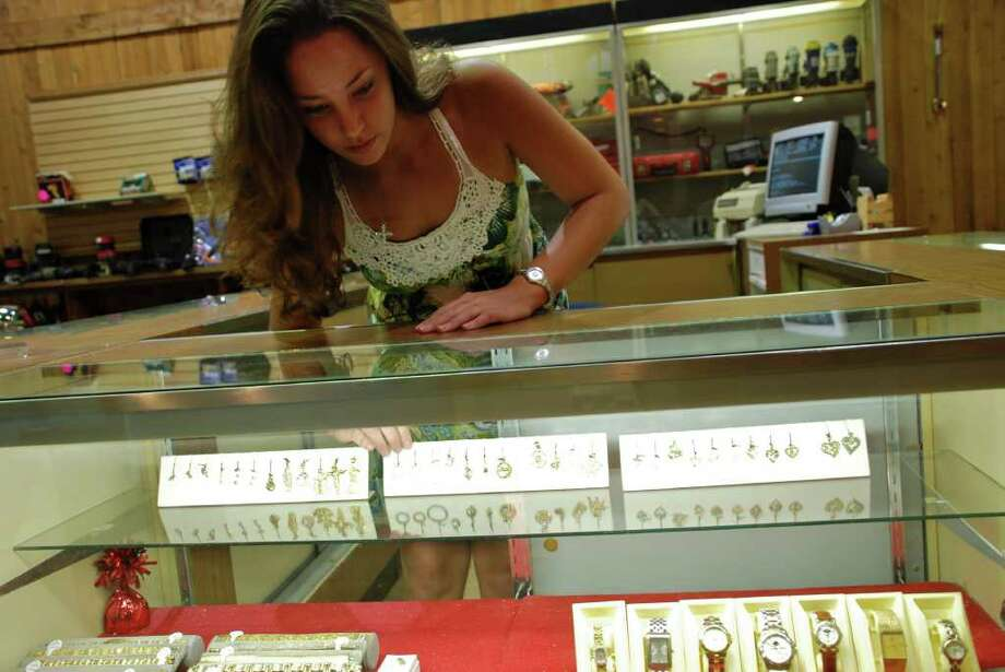 LINDSAY PEYTON PHOTOS: FOR THE CHRONICLE ALL THAT GLITTERS: Gallery Pawn manager Jessica Lowry arranges items in the jewelry case. She said that gold and guns are the best sellers in the shop. Photo: Lindsay Peyton
