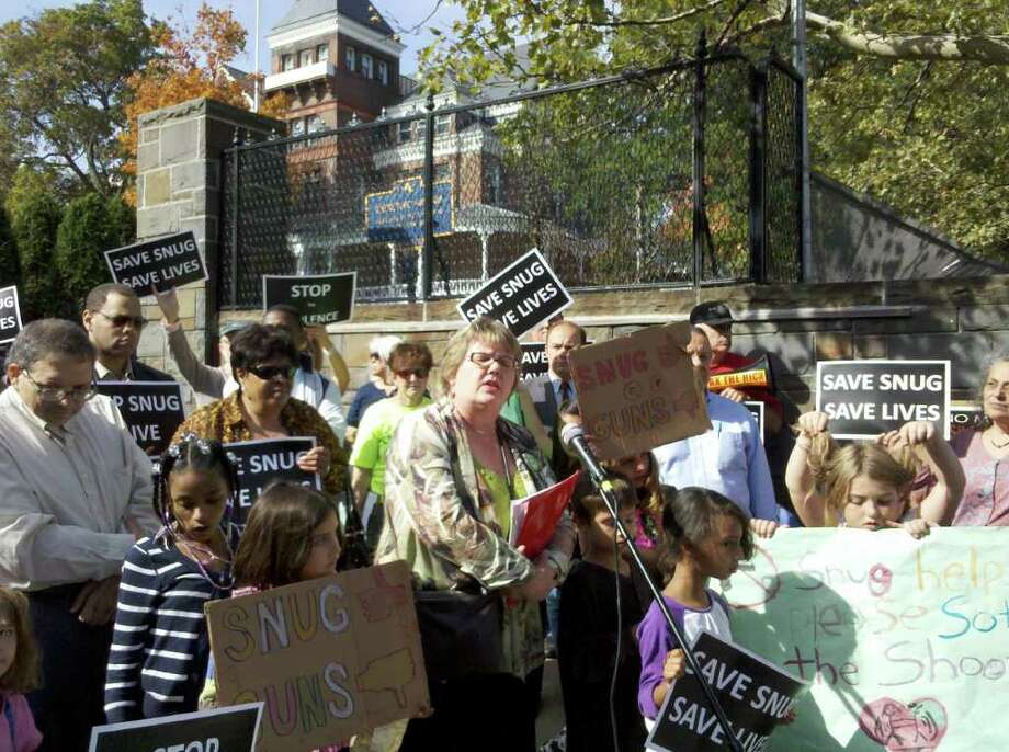 About 100 community activists, residents and politicians rallied Tuesday morning outside the Executive Mansion on Eagle Street to protest the closing of an anti-violence program known as Operation SNUG amid state budget cuts.
