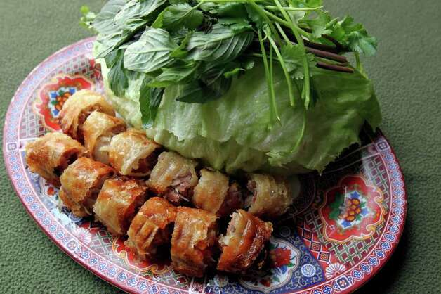 Thick spring rolls only get better with the accompanying lettuce leaves, cilantro sprigs and Vietnamese fish sauce. TOM REEL / EXPRESS-NEWS Photo: TOM REEL, SAN ANTONIO EXPRESS-NEWS / © 2011 San Antonio Express-News