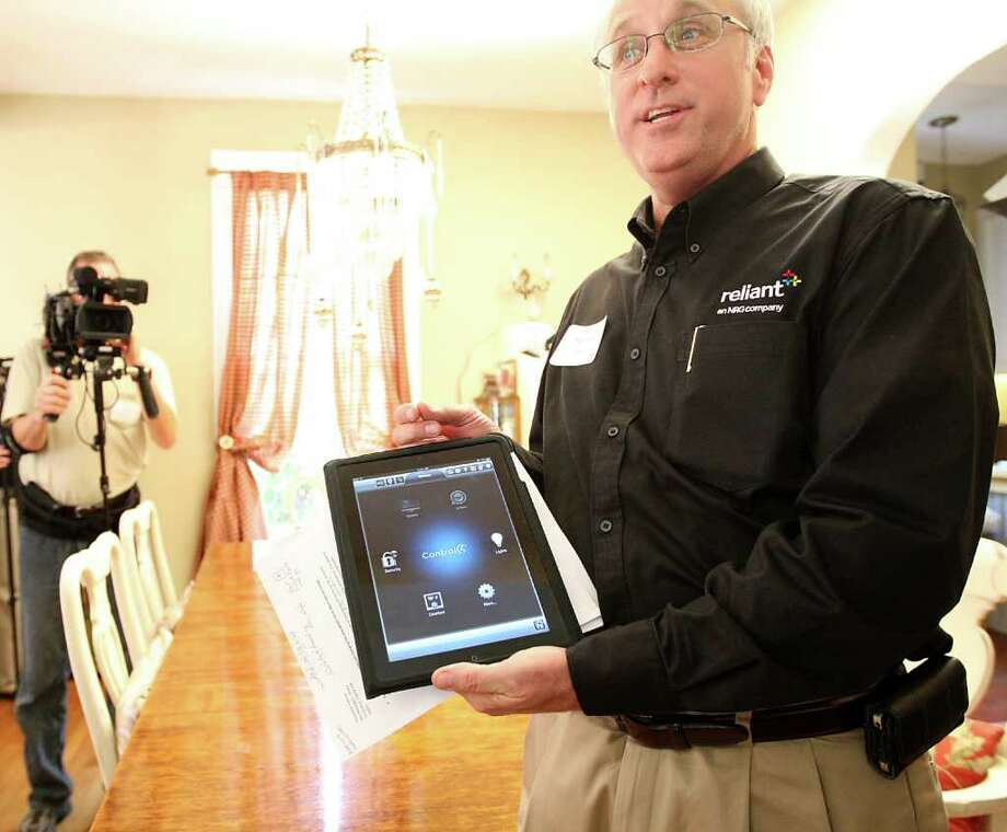 "Wayne Morrison, manager of Smart Energy, demonstrates the Reliant e-Sense App while on a tour of a home, where Reliant Energy outfitted twelve families with smart meters and accessories, on a street called ""Reliant Innovation Avenue"".  The technology that was showcased included home energy monitors, smart appliances and home automation and solar panels. Mayor Annise Parker and home improvement expert, Bob Vila, were on hand at the event. Photo: Karen Warren, Houston Chronicle / © 2011 Houston Chronicle"