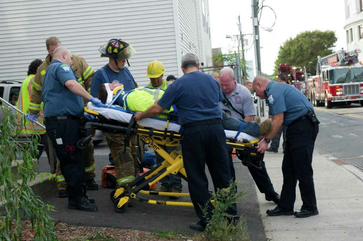 Paramedics tend to a worker at an excavation site who became trapped under a car that drove into a three-foot deep ditch on Henry Street in Stamford, Conn., October 11, 2011. The driver, a 73-year-old man, turned onto Henry Street, which was closed to west-bound traffic because of the construction. The driver hit a 19-year-old excavation worker and his car fell into the trench, trapping the worker underneath. Co-workers dug him out from the ditch, and paramedics took him to Stamford Hospital, his injuries were not serious. The excavation contractor, A.J. Penna and Son, was doing work for Connecticut Light & Power, Montagnese said.