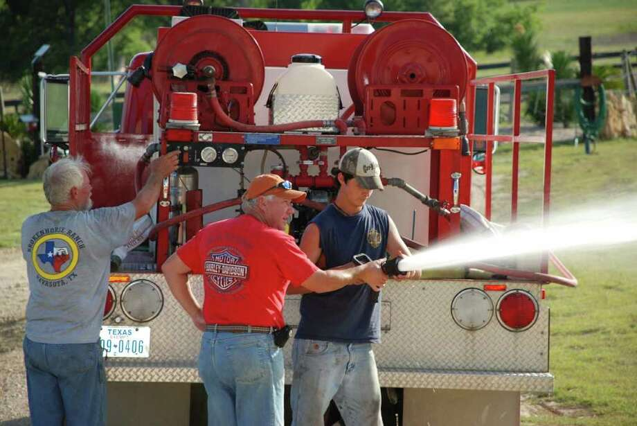 Roger Lieder, son of Mildred and Lawrence Lieder, trains Cy-Fair volunteer firefighter Christopher Vickers, 19, how to use the fire hose nozzle, which controls water flow.
